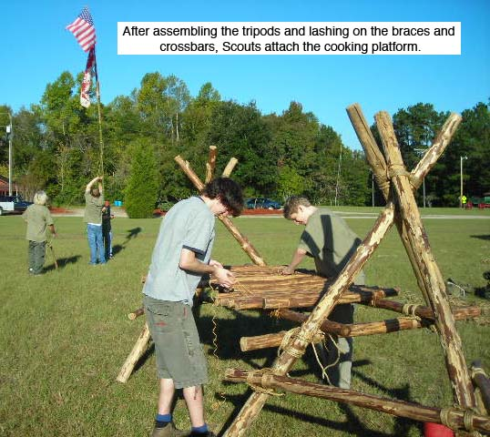 After assembling the tripods and lashing on the braces, Scouts lash on the cooking platform on a Double Tripod Chippewa Kitchen