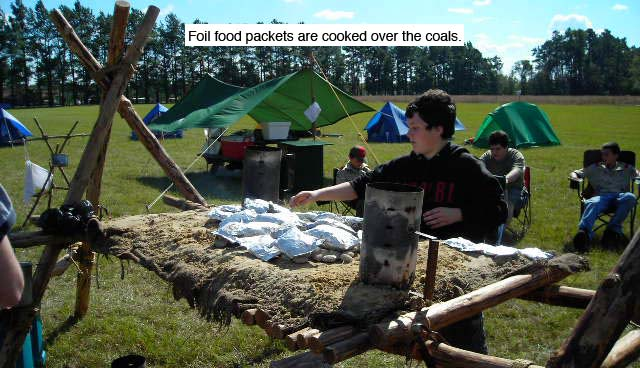 Foil food packets are cooked over the coals on a Chippewa Kitchen