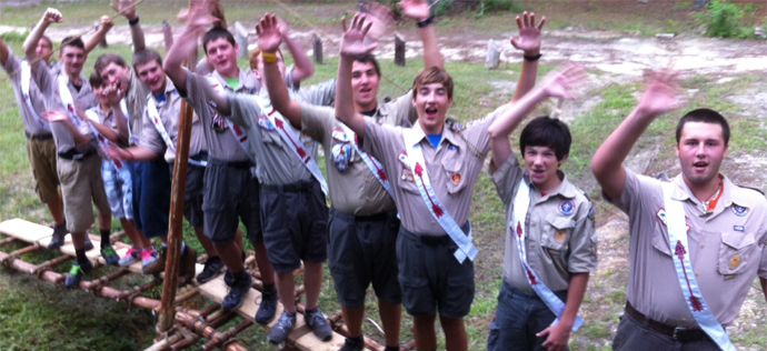 Scouts wave from a Single A-Frame Bridge built by the Pioneering Merit Badge Class during OA Week at Camp Coker.