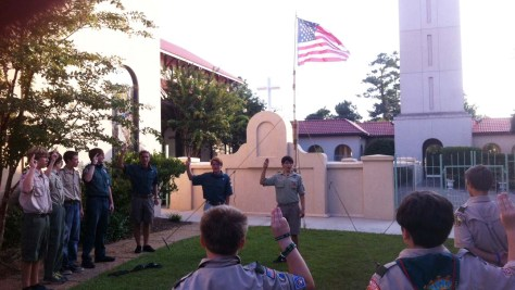 During the gathering period, a flagpole is lashed together using four Scout staves. A carabiner is tied to the top, a halyard is strung through, and the pole is lifted and secured with three guy lines. The flag is raised as part of the troop's opening ceremony.