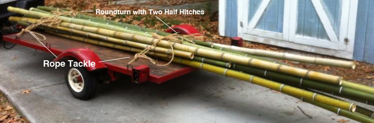 Securing a load of spars to a flatbed for transport.