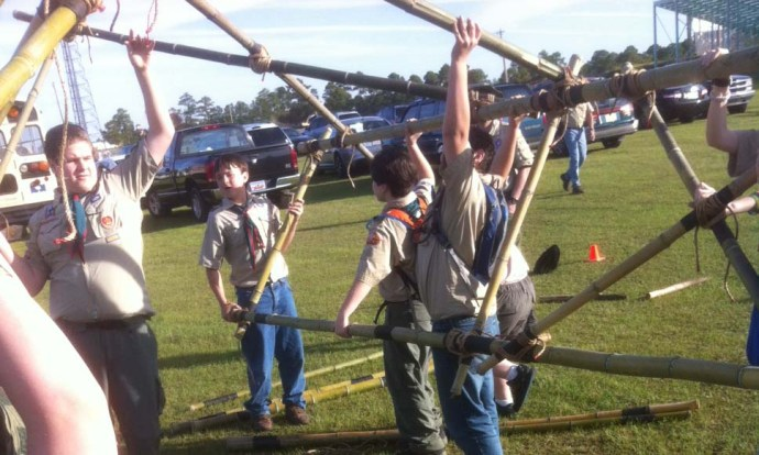Scouts carefully lift the structure and rotatie it 180° to lash the other side.
