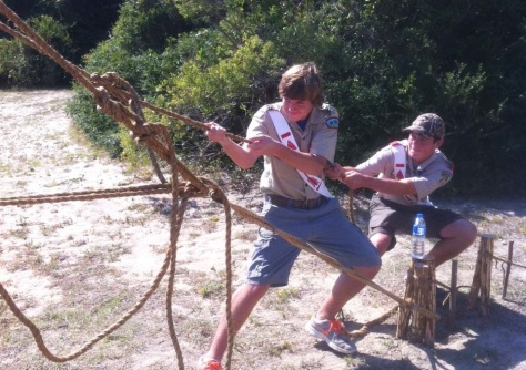 Using a Rope Tackle, two Scouts tighten a hand rope on their monkey bridge.