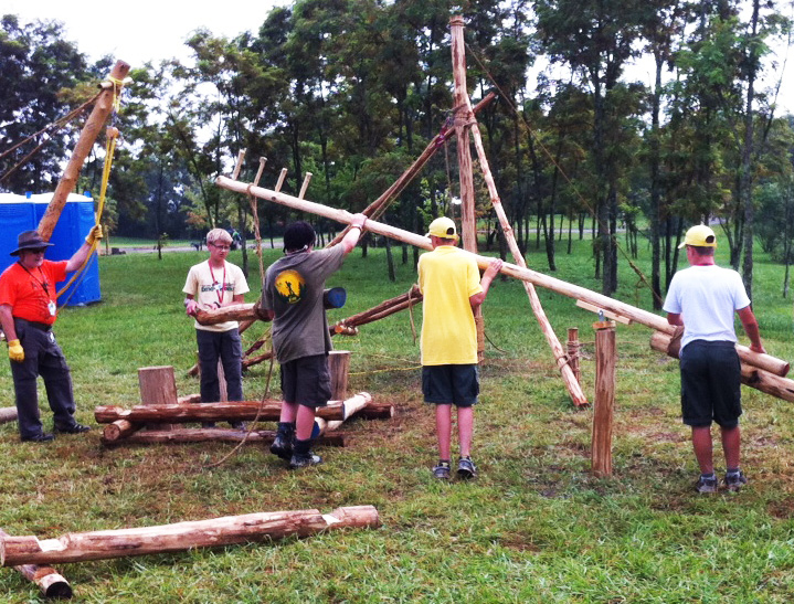 A Boom Derrick could be placed at each corner of the log cabin construction site.