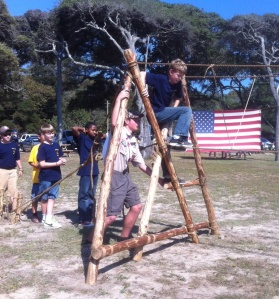 "A member of Santee Lodge, 116, Ordeer of the Arrow, helps Webelos Scouts cross the monkey bridge his chapter built during a District ""Webeloree."""