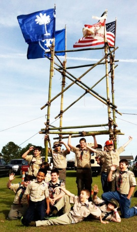 Scouts strike a pose after hoisting their Four Flag Gateway Tower at a Scout Expo.